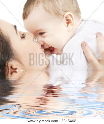 Happy Mother Kissing Baby Boy In Water