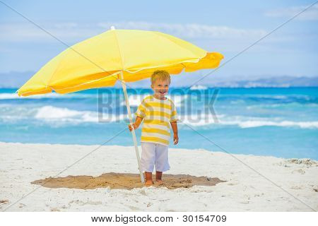 Boy with big umbrella on tropical beach