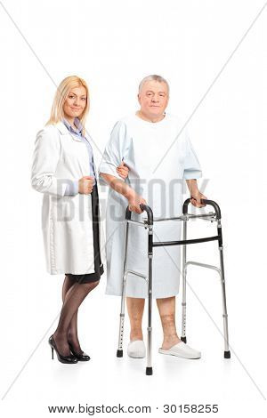 Full length portrait of a female doctor or nurse helping a senior patient to use a walker isolated on white background