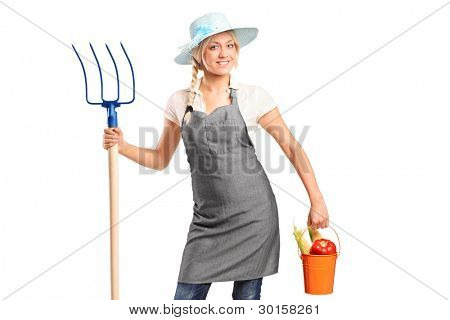 A female farmer holding a pitchfork and bucket with vegetables isolated on white background