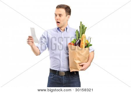 A surprised man looking at store receipt and holding a paper bag isolated on white background