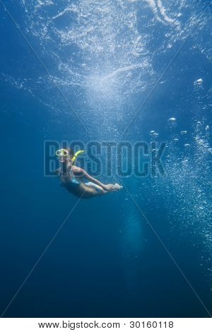 Young woman diving into deep on a breath