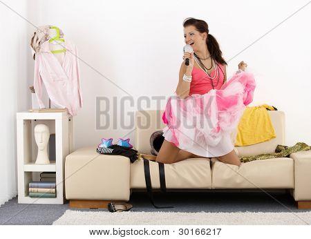 Pretty teenage girl having fun at home, singing, posing, laughing.?