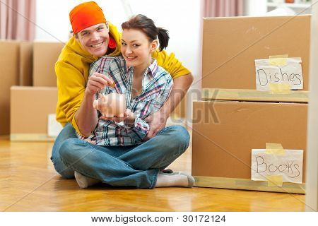 Young Couple Among Boxes Putting Coin In Piggy Bank