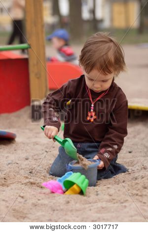 Little Girl Playing At Sand-Box