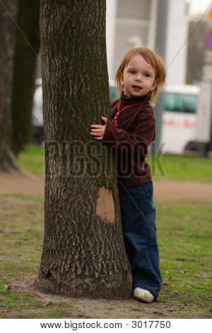 Small Beauty Girl Playing Hide-And-Seek At The Park.