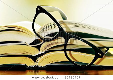 a pile of books and glasses symbolizing the concept of reading habit or studing