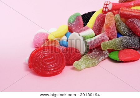 a pile of candies on a pink background
