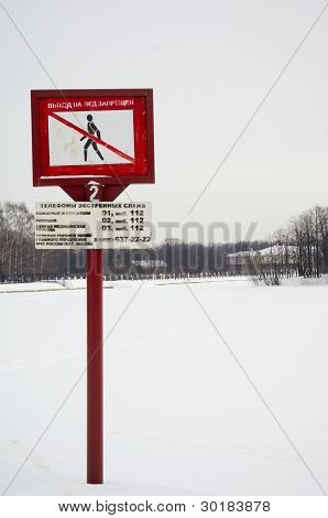 Frozen Lake In Winter And Warning Sign