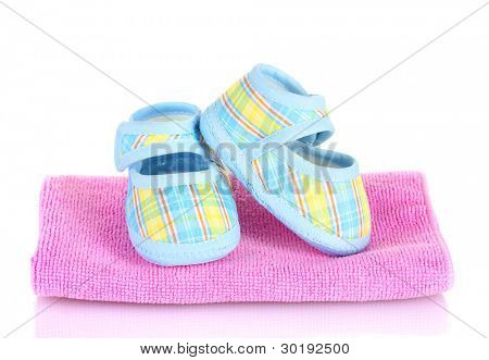 Botitas de bebé de azul en rosa toalla aislado en blanco