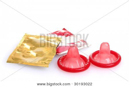 Red condoms with  open packs isolated on white