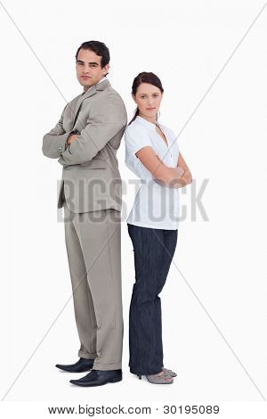 Serious sales team with arms folded standing back to back against a white background