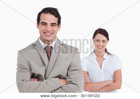 Smiling business team with arms crossed against a white background