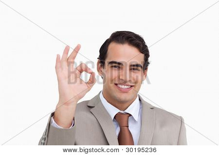 Close up of smiling salesman giving his approval against a white background
