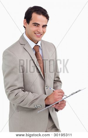 Smiling salesman with notepad and pen against a white background