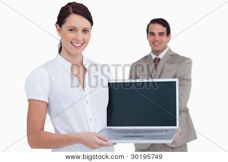 Smiling saleswoman presenting laptop screen with colleague behind her against a white background