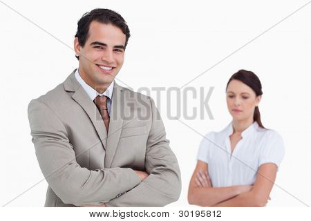 Smiling salesman with colleague behind him against a white background