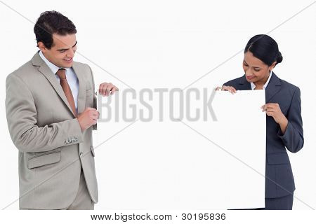 Sales team holding and looking at blank sign against a white background