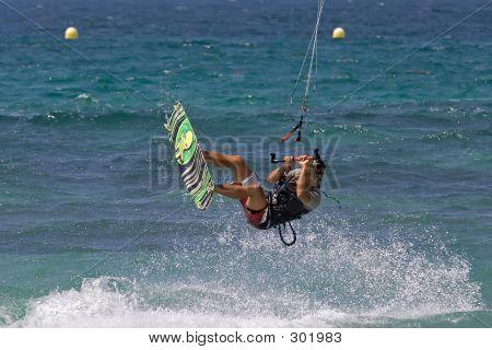 Kitesurfer Flying Through The Air On A Sunny Beach