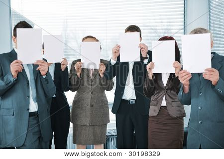 Business team holding white papers in office