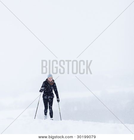 Cross-country skiing: young woman cross-country skiing on a snowy winter day