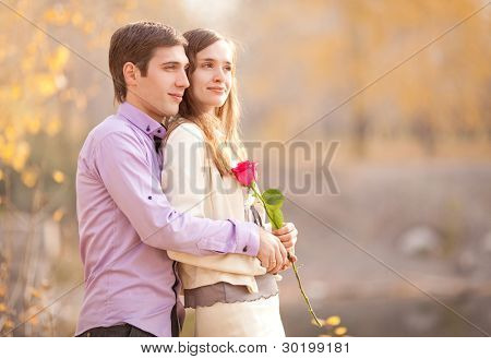 happy young couple spending time outdoor in the autumn park (focus on the man)