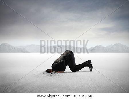Empresario escondiendo la cabeza en la arena