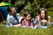Mother Is Blowing Bubbles While Lying On The Blanket In The Park With Husband And Daughter. Husband  poster
