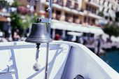 Boat Tour: Boat Bow With Boat Bell, View Over Azure Blue Water, Mountain Range And Little Village. L poster