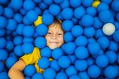 Child Playing In Ball Pit. Colorful Toys For Kids. Kindergarten Or Preschool Play Room. Toddler Kid  poster
