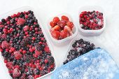 stock photo of tupperware  - Plastic containers of frozen mixed berries in snow  - JPG
