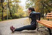 Photo of a beautiful pretty young pretty fitness woman outdoors in the park make sport exercises. poster