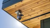 Panorama Home With Security Camera Installed On The Wooden Underside Of Its Roof poster