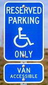 Vertical Blue Reserved Parking Van Accessible Sign With A Man On A Wheelchair Icon poster