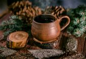 Pot Of Hot Herbal Tea, Fir Cones And Paws Of Blue Fir On Wooden Background poster