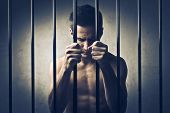 stock photo of delinquency  - Young man in prison - JPG
