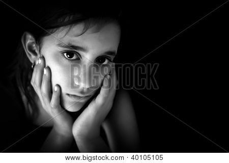 Portrait of a sad hispanic girl in black and white with space for text
