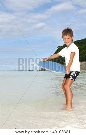 young boy with skim board on sea background