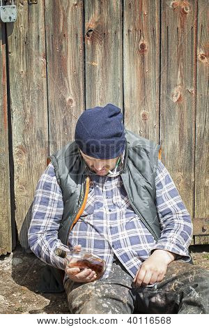 Homeless leaning against barn door