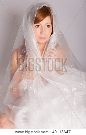 The Young Woman Sitting Wrapped In Foil On The Floor