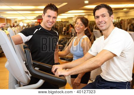 Three Friends On Exercise Bikes In A Gym