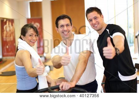 Three Friends In Gymnasium Giving Thumbs Up