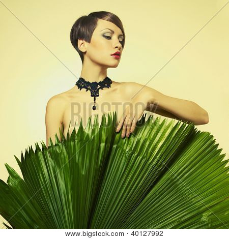 Portrait of beautiful stylish lady with palm leaves