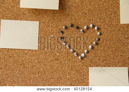 Heart Made Form Pins On Cork Office Board With Papers