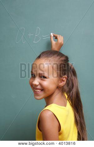 Escuela chica escribir en la pizarra