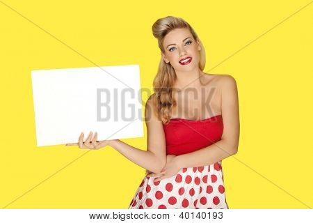Glamorous smiling blonde woman with bare shoulders holding a blank sign for your text or advertisement isolated on a bright yellow studio background