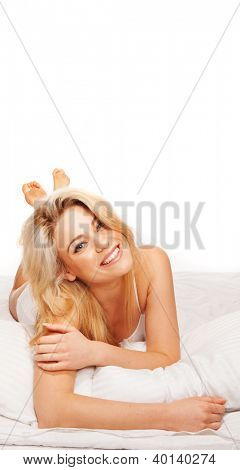 Fresh studio portrait of a gorgeous vivacious blonde woman lying on her bed in lingerie facing the camera laughing with plenty of copyspace overhead