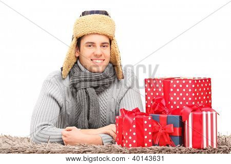 A smiling guy with hat and neckwear lying on a carpet near presents isolated against white background