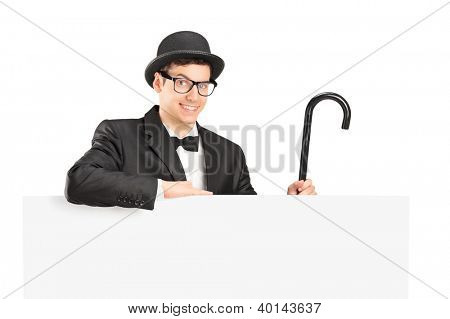 A performer in black suit, retro hat and cane posing behing a blank panel isolated on white