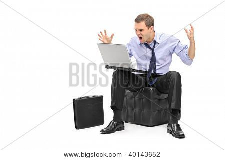 A nervous young businessman screaming on his laptop isolated against white background